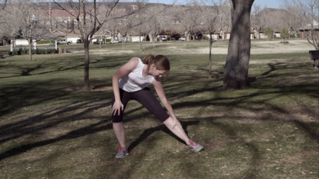 woman in athletic clothing stretching in the park. - ランニングショートパンツ点の映像素材/bロール