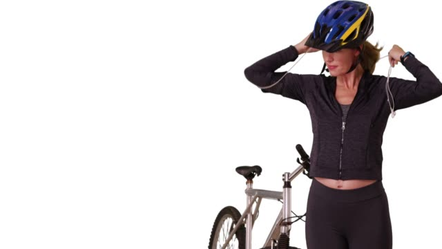 stockvideo's en b-roll-footage met woman in athletic gear going for bike ride on white background with copy space - hoofdtelefoon
