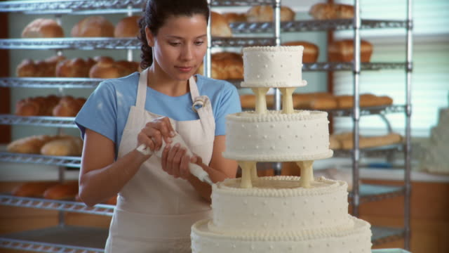 TU Woman in bakery decorating wedding cake and smiling at camera / racks of bread in background