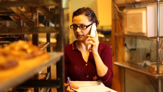 vídeos de stock e filmes b-roll de woman in bakery talking on phone - telefone sem fio