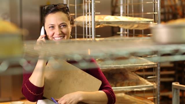 woman in bakery talking on phone