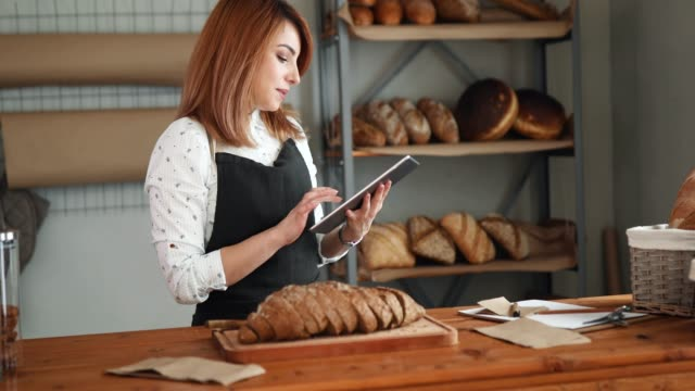 woman in bakery using tablet - bakery stock videos and b-roll footage