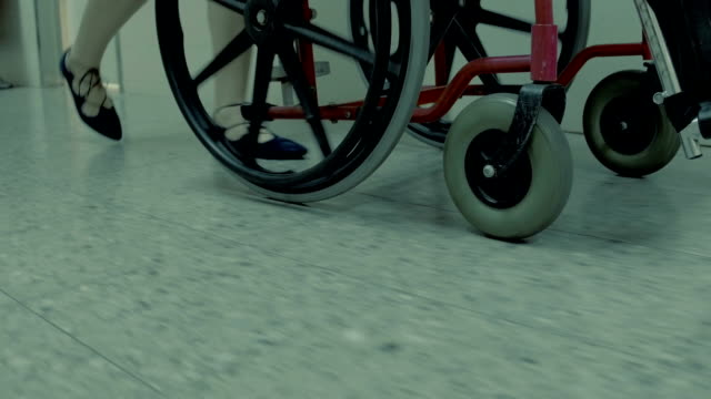 woman in ballet flats rolling an empty wheelchair - wheel stock videos & royalty-free footage