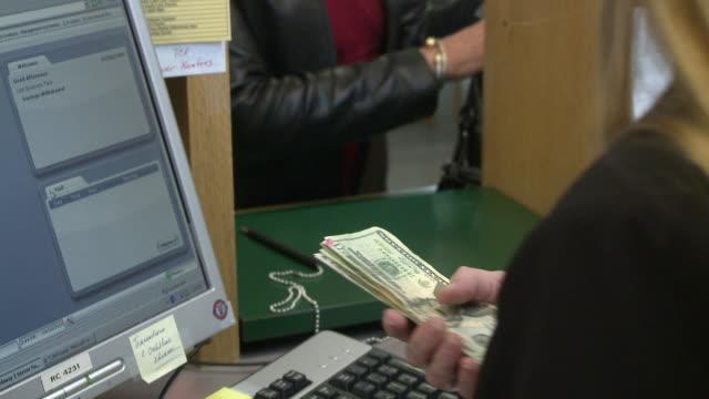 CU TU Woman in bank making withdrawal and talking on phone, Bethlehem, Pennsylvania, USA
