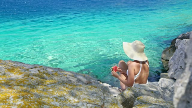 woman in bathing suit and sun hat eating fresh watermelon along tranquil blue ocean - sun hat stock videos & royalty-free footage