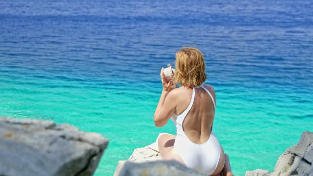 Woman in bathing suit holding seashell up to ear at sunny summer blue ocean