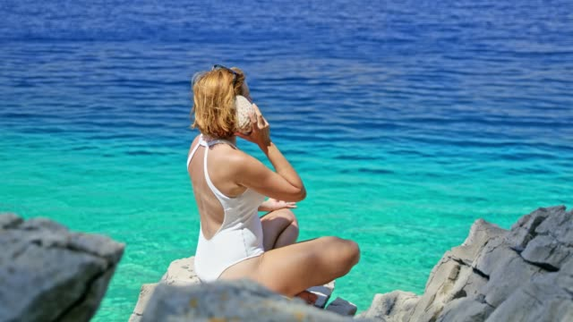 woman in bathing suit meditating,holding seashell up to ear at sunny summer blue ocean - animal shell stock videos & royalty-free footage