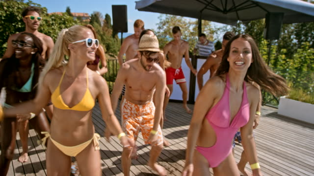 Woman  in bathing suit posing for the camera while dancing a group dance with her friends at a pool party