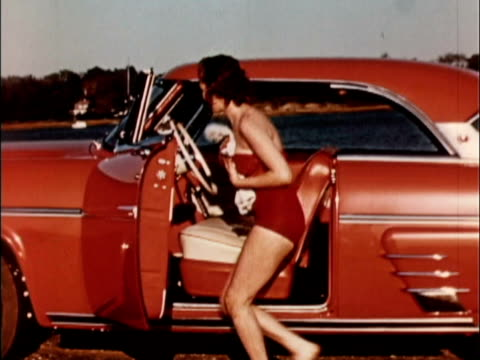 vídeos y material grabado en eventos de stock de 1956 montage woman in bathing suit sitting down on front seat of red 1953 mercury monterey. she dries herself with towel / usa - traje de baño de una pieza