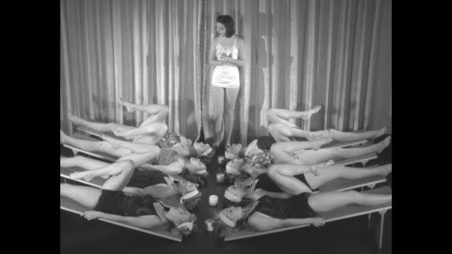vidéos et rushes de woman in bathing suit standing between two rows of women in bathing suits in front of teacher anne delafield sitting at desk / close shot of... - mascara