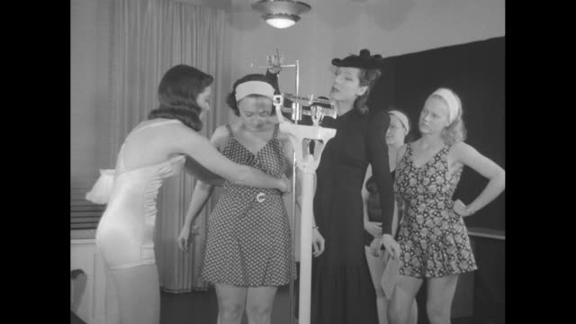 woman in bathing suit walks up to desk where instructor anne delafield is sitting and models bathing suit / two shots of women being weighed on scale... - tape measure点の映像素材/bロール