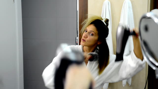 Woman in bathrobe in bathroom drying her hair with fan