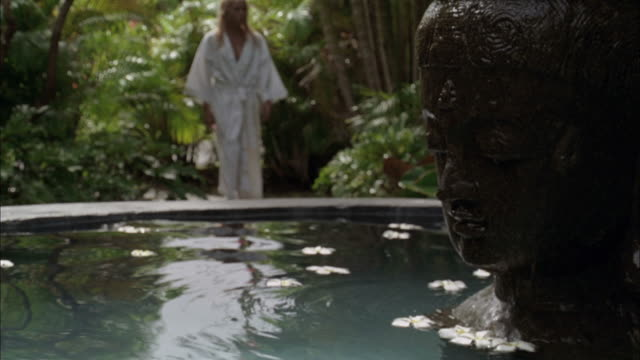 SLO, MO, SELECTIVE FOCUS, Woman in bathrobe passing by fountain in tropical surroundings, mid section, Maui, Hawaii, USA, SLO MO