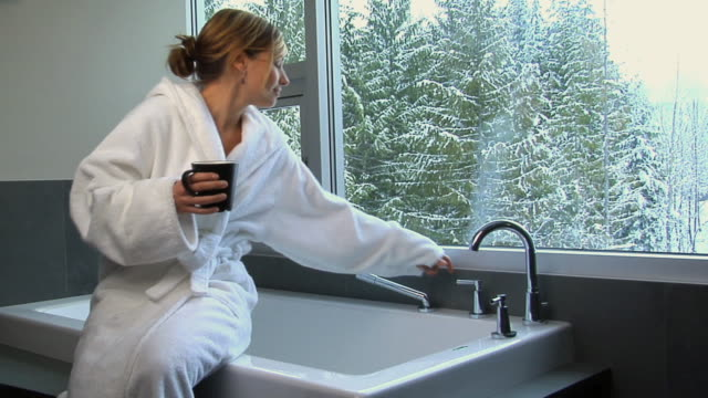 MS Woman in bathrobe sitting on bathtub having drink, opening faucet and looking through window / Whistler, British Columbia, Canada