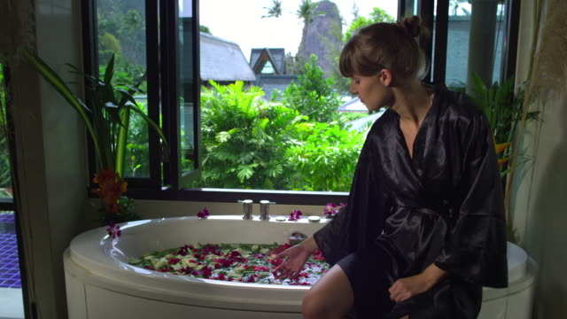 MS Woman in bathrobe sitting on spa bath with rose-petals, Krabi, Thailand