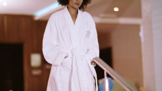 woman in bathrobe standing at poolside - spa stock videos & royalty-free footage