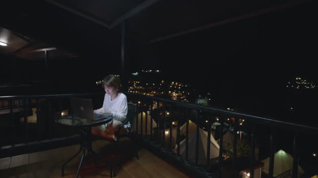 woman in bathrobe using laptop at night time in hotel suite - bathrobe stock videos & royalty-free footage