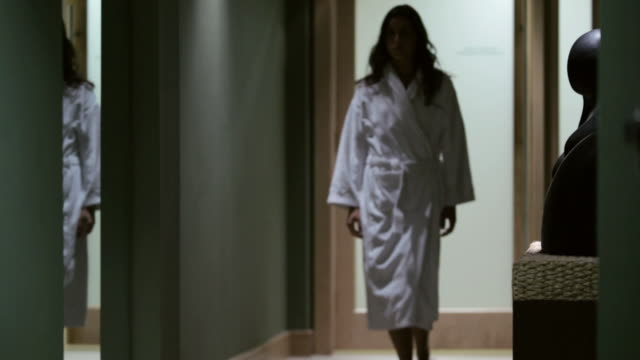MS Woman in bathrobe walking through door / Stowe, Vermont, United States