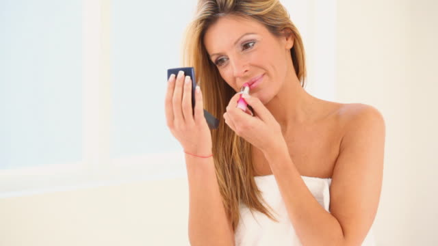 stockvideo's en b-roll-footage met hd1080 woman in bathroom applying lipstick. - in een handdoek gewikkeld