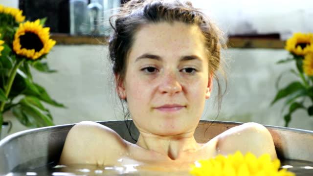 woman in bathtub with sunflower - körperpflege stock-videos und b-roll-filmmaterial