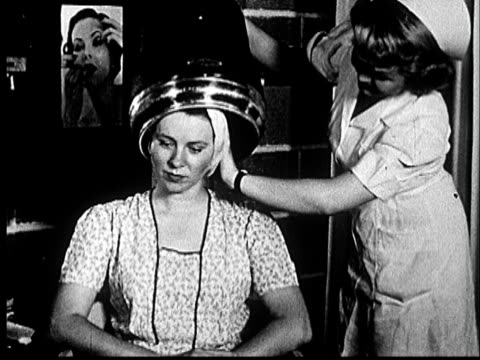 1953 ms woman in beauty parlor with head in hair dryer, chewing gum as she smiles and nods at nurse/ norman, oklahoma - beauty salon stock videos and b-roll footage