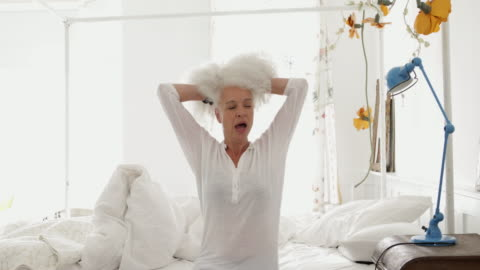 woman in bed waking up in the morning - white hair stock videos & royalty-free footage