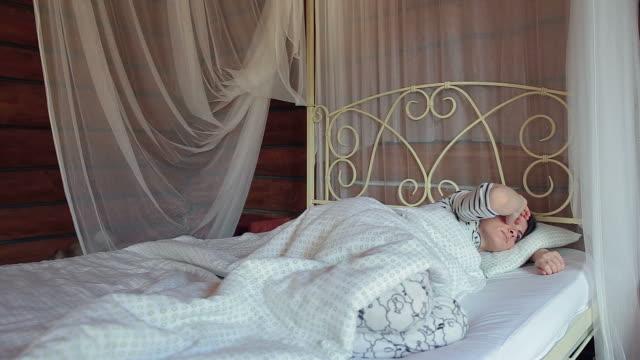 frau im bett bestätigt den wecker auf der mobiltelefon. - napping stock-videos und b-roll-filmmaterial