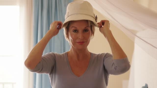 vidéos et rushes de woman in bedroom putting on hat. - chapeau