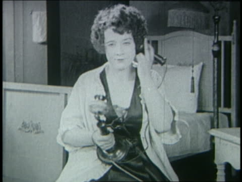 b/w 1925 woman in bedroom talking on telephone / silent film - anno 1925 video stock e b–roll