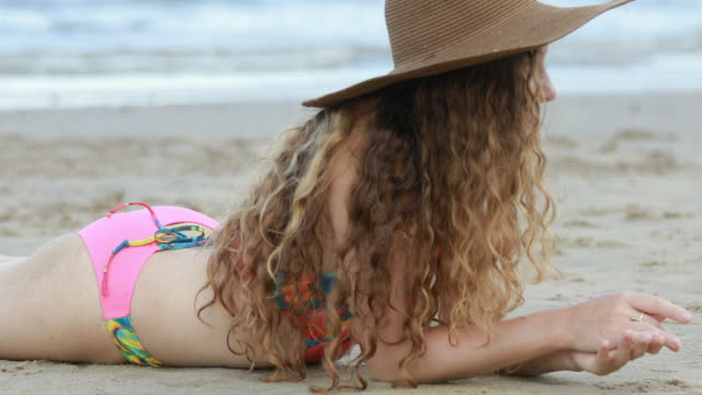 woman in bikini and summer hat lying on tropical beach