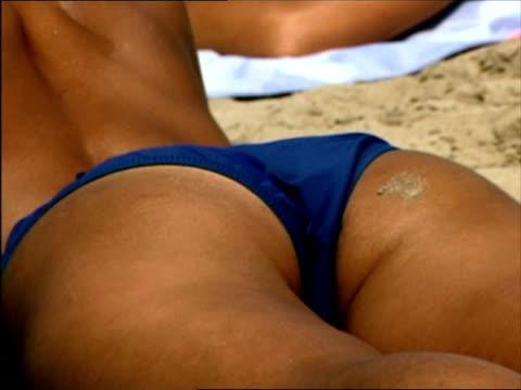CU, Woman in bikini button sunbathing on beach, rear view, mid section, Ibiza, Spain