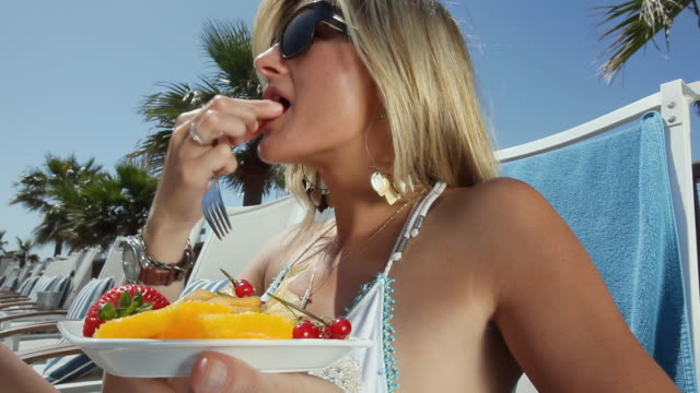 cu woman in bikini lying on deck chair, eating fruit from plate / golf de son termes, bunyola, mallorca, baleares, spain - in den dreißigern stock-videos und b-roll-filmmaterial