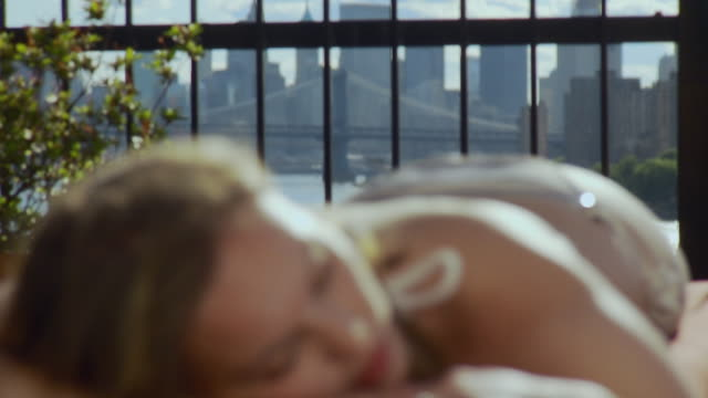 cu td r/f woman in bikini napping on lounge chair, with manhattan skyline behind / new york city, usa - reclining stock videos & royalty-free footage