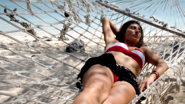 Woman in bikini on a hammock at the beach in Gili Trawangan Island in Bali