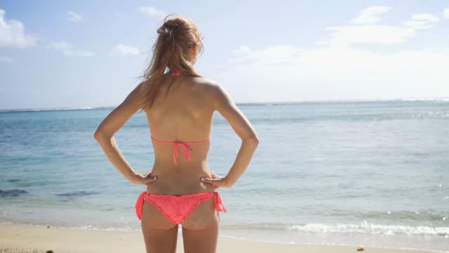 Woman in bikini on sandy beach, soaking up summer sun