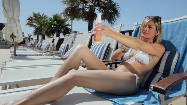 MS Woman in bikini sitting on deckchair applying sun cream / Golf De Son Termes, Bunyola, Mallorca, Baleares, Spain