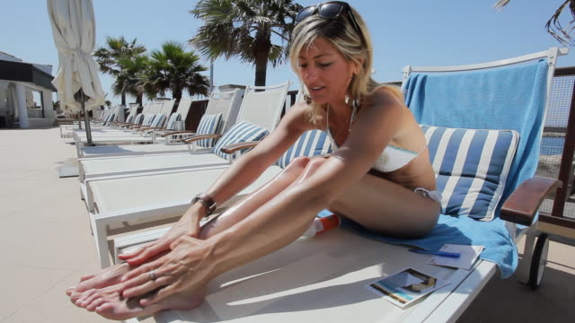 ws woman in bikini sitting on deckchair applying sun cream / golf de son termes, bunyola, mallorca, baleares, spain  - sonnencreme stock-videos und b-roll-filmmaterial