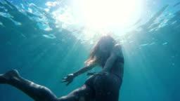 Woman in Bikini swimming underwater towards surface like a mermaid with beautiful sun flares in slow motion.