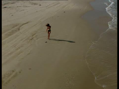 aerial ws zo woman in bikini walking along beach, carmel, israel - endast unga kvinnor bildbanksvideor och videomaterial från bakom kulisserna