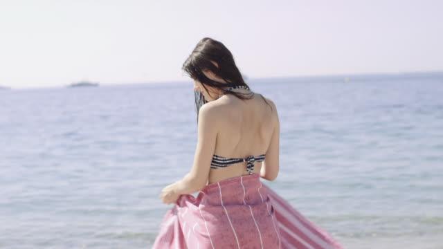 woman in bikini wrapping towel around on beach - タオルにくるまる点の映像素材/bロール