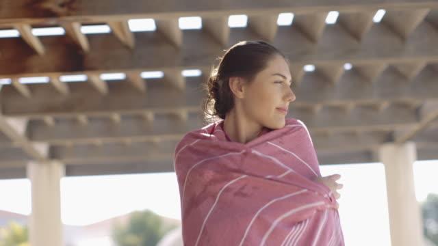 woman in bikini wrapping towel around - avvolto video stock e b–roll