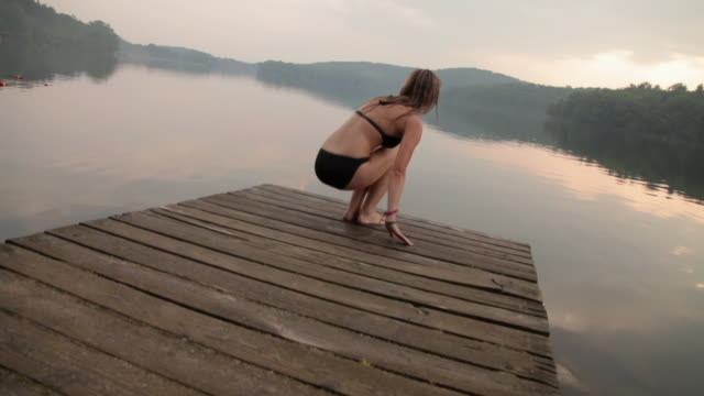 Woman in black bikini standing on pier by lake