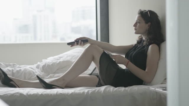 woman in black dress and heels uses television remote in hotel room, medium shot - black dress stock videos & royalty-free footage