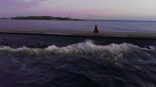 woman in black dress dances at rocky pier at sunset with view over lighthouse aerial - black dress stock videos & royalty-free footage