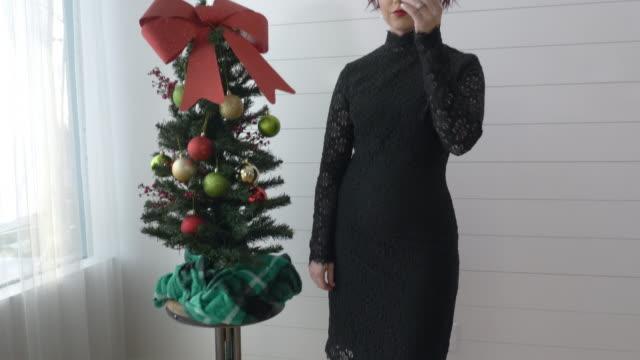 woman in black dress posing next to christmas tree - black dress stock videos & royalty-free footage