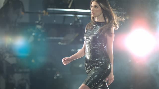 woman in black dress walking on a catwalk tossing her hair. - model stock-videos und b-roll-filmmaterial
