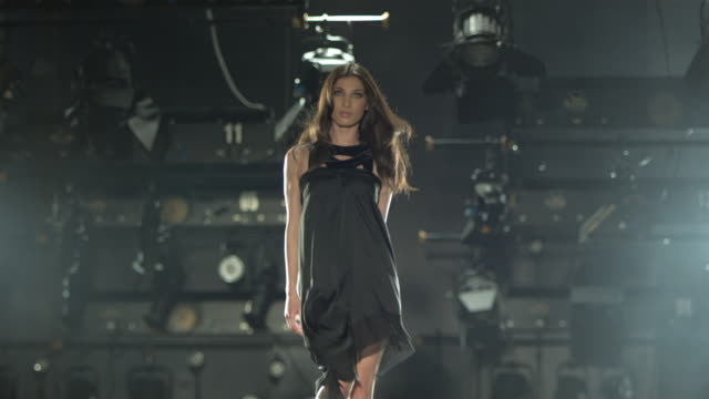 Woman in black dress walking on a catwalk towards camera and tossing her hair.