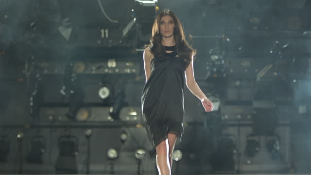 woman in black dress walking on a catwalk towards camera and tossing her hair. - catwalk stock videos & royalty-free footage