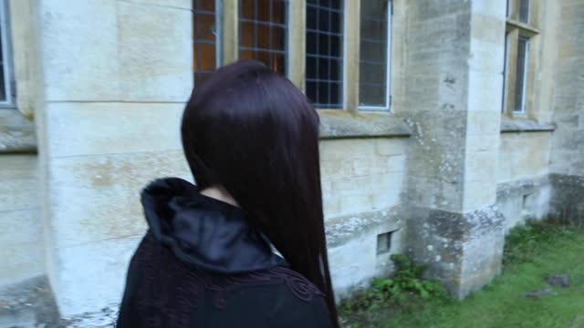 woman in black robes walking beside old brick building - nazi-era historic reenacment - holocaust stock videos & royalty-free footage