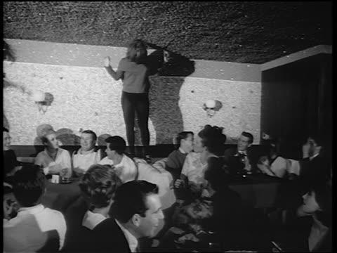 B/W 1965 woman in black tights dancing on table in nightclub as crowd claps / newsreel